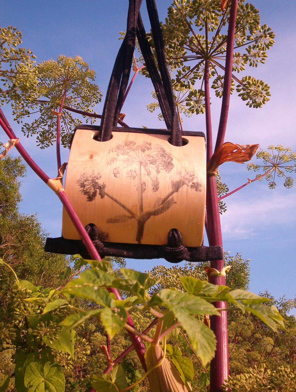 puu pildiga puidust kott, mis on puude keskel