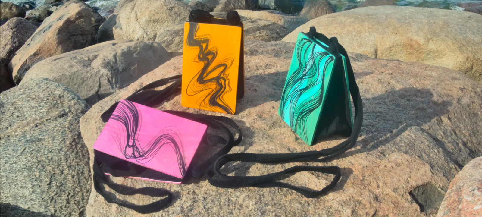 Three bags with décor—pink, yellow, and green—on a rock