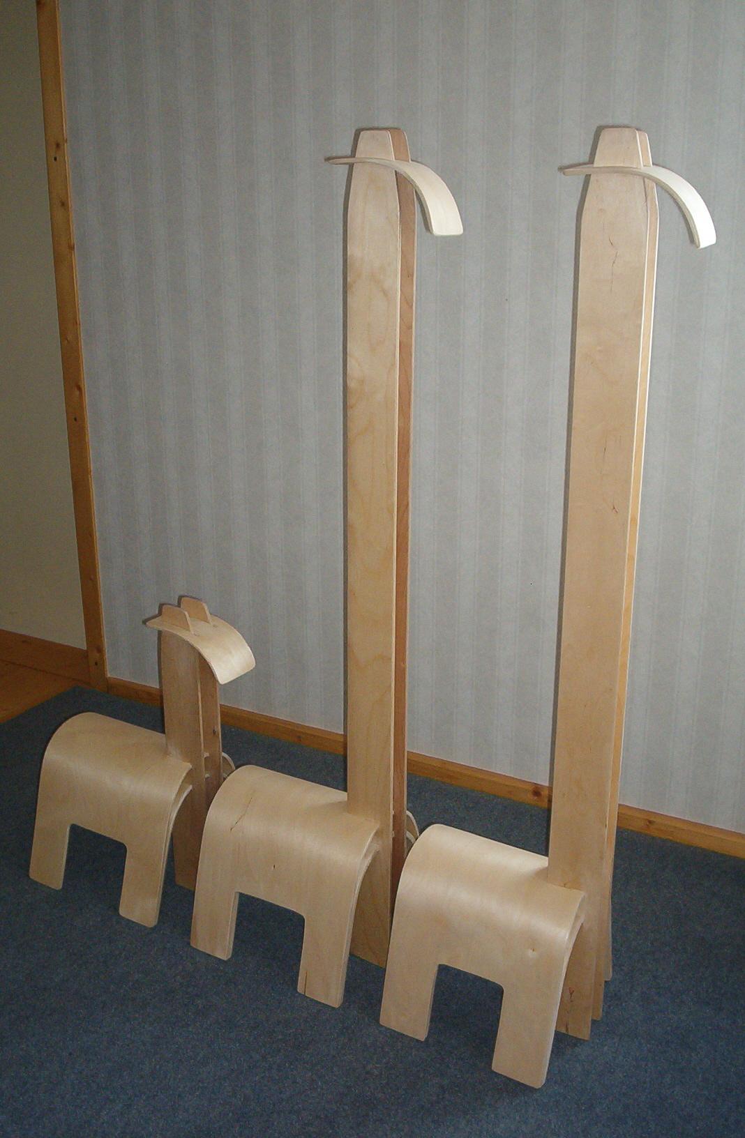 smaller wooden horse next to two wooden giraffes