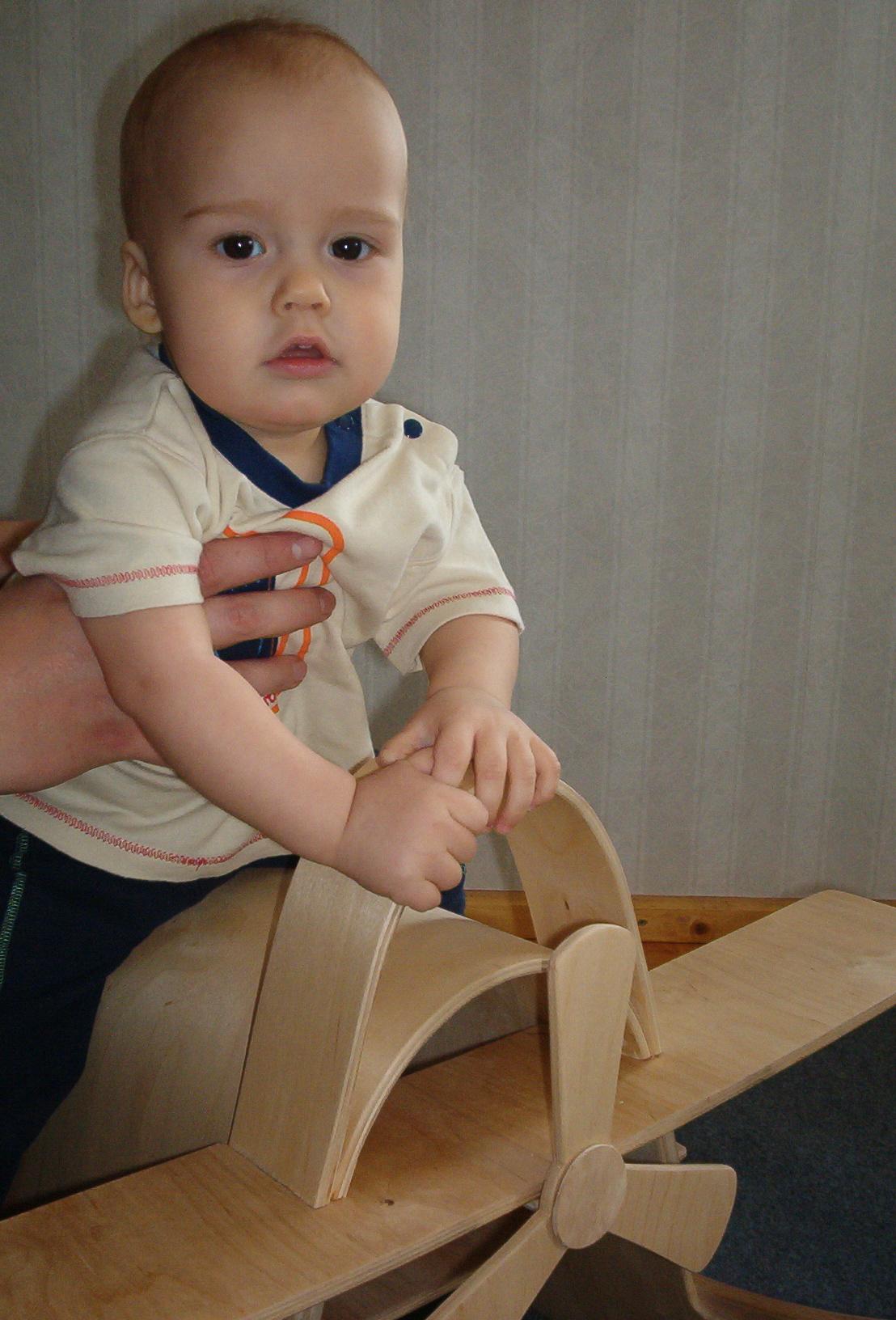 child sitting on a toy plane