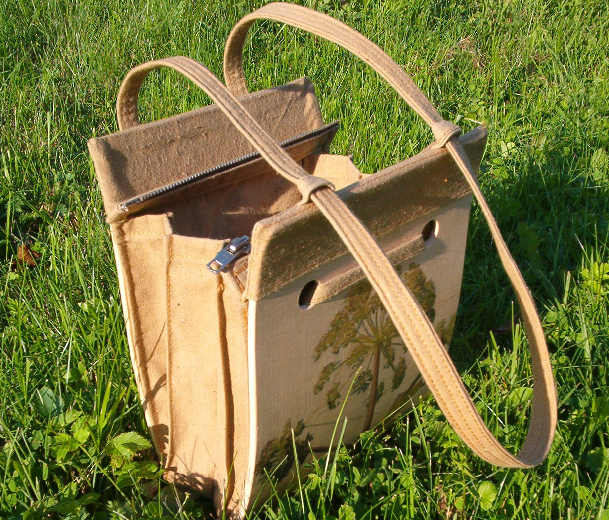 larger wooden bag with a picture of an oak, laying on the grass
