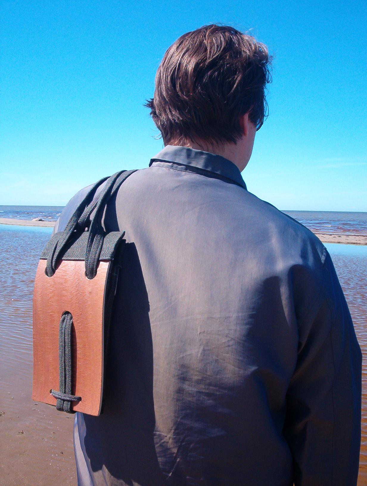 man wearing a wooden bag on his shoulder