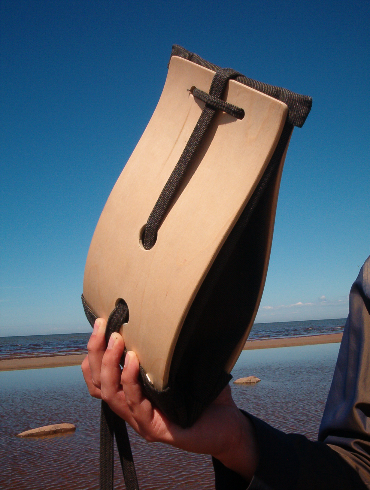 man holding a wooden bag in his hand