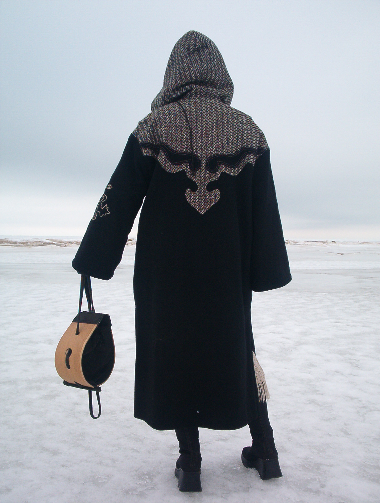 woman wearing a black-grey coat with a large wooden bag in hand