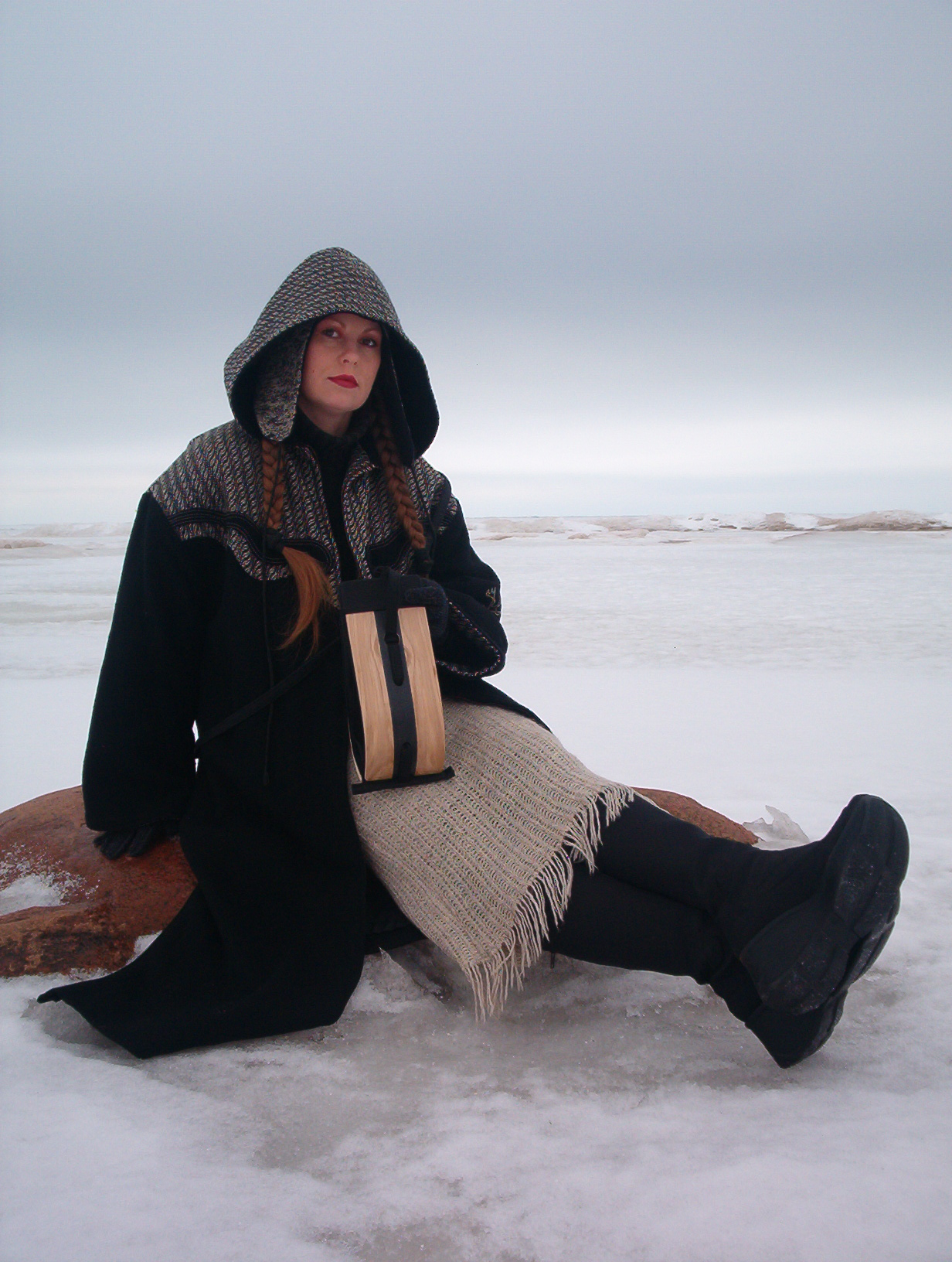 woman sitting on rock with wooden black and white intarsia bag in the lap